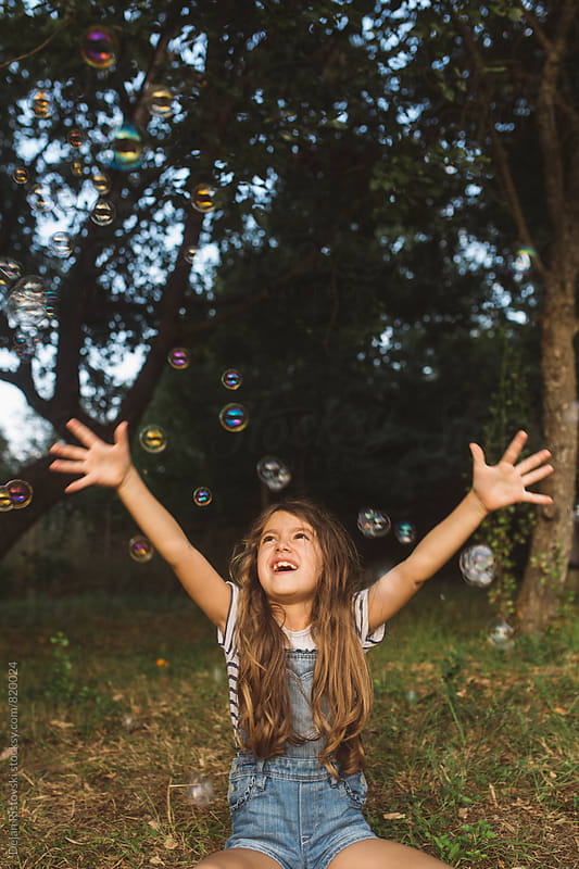 Child playing catching bubbles. by Dejan Ristovski for Stocksy United