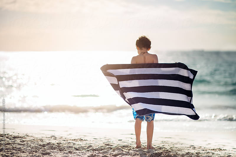 Boy with a towel after a swim at the beach by Angela Lumsden for Stocksy United