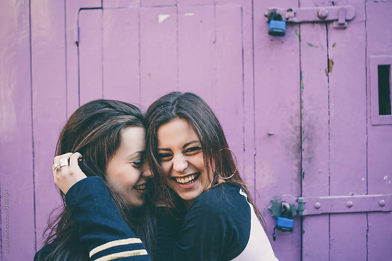 Twin teenage girls laughing and hugging. by kkgas for Stocksy United