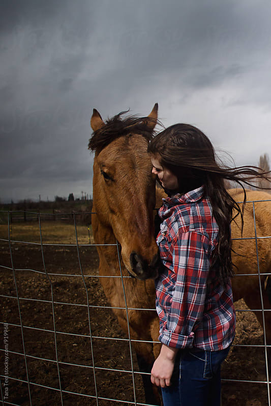 young woman stands by horse on windy day by Tana Teel for Stocksy United