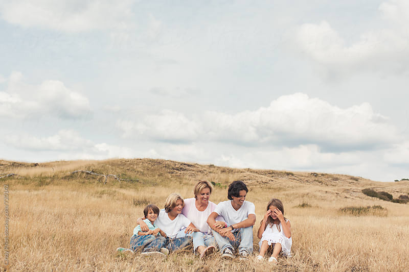 Grandmother and her grandkids sitting in a golden field underneath a big sky by Cindy Prins for Stocksy United