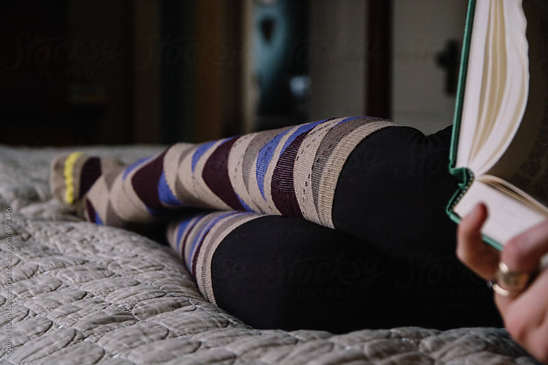 Woman holding a book laying on a bed wearing argyle pattern knee-high socks by Gabriel (Gabi) Bucataru for Stocksy United