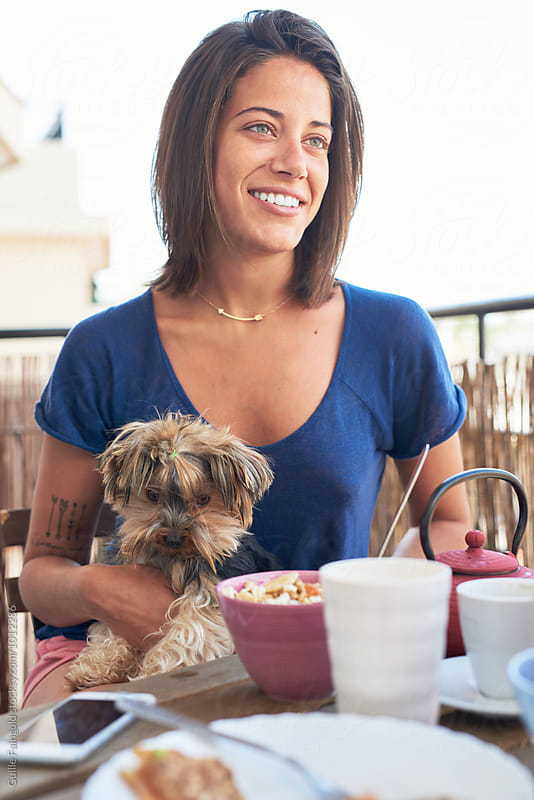 Beautiful smiling woman with pet dog at breakfast table outdoor by Guille Faingold for Stocksy United