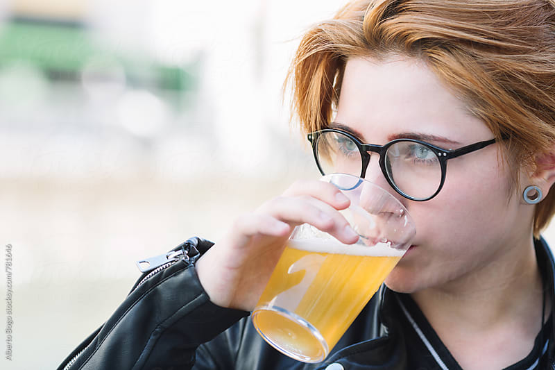 Young woman holding a glass of beer by Alberto Bogo for Stocksy United