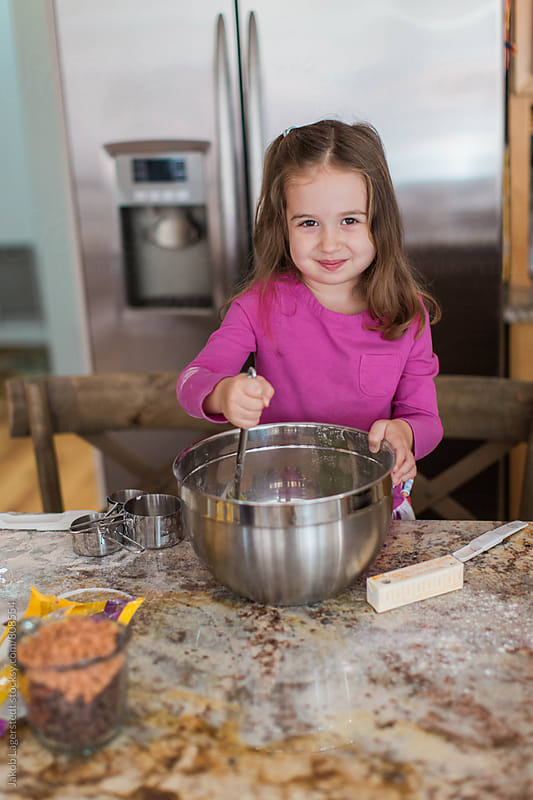 Cute little young girl baking cookies in a kitchen by Jakob for Stocksy United