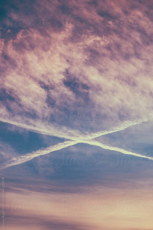 cross created by planes in the sky at sunset by Javier Pardina for Stocksy United