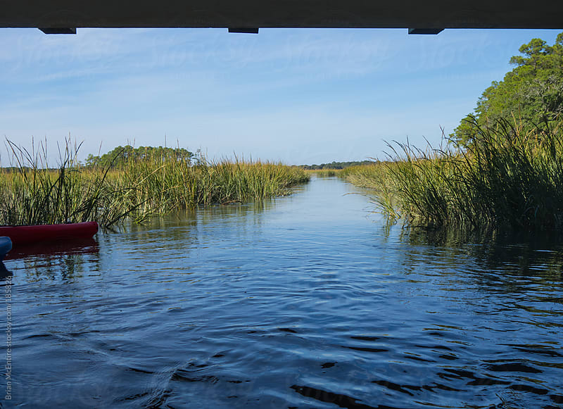 Kayaking Under Bridge over Tidal River in Carolina Low Country by Brian McEntire for Stocksy United