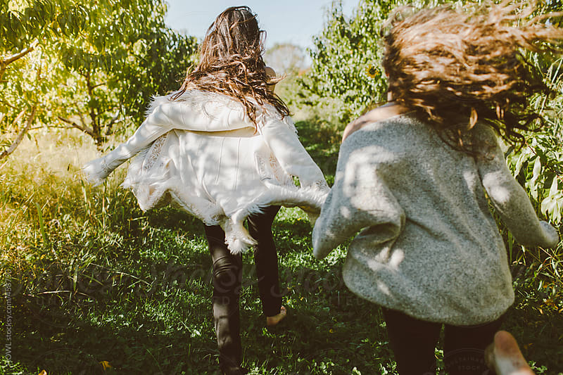 Two best friends run barefoot in an apple orchard by HOWL for Stocksy United