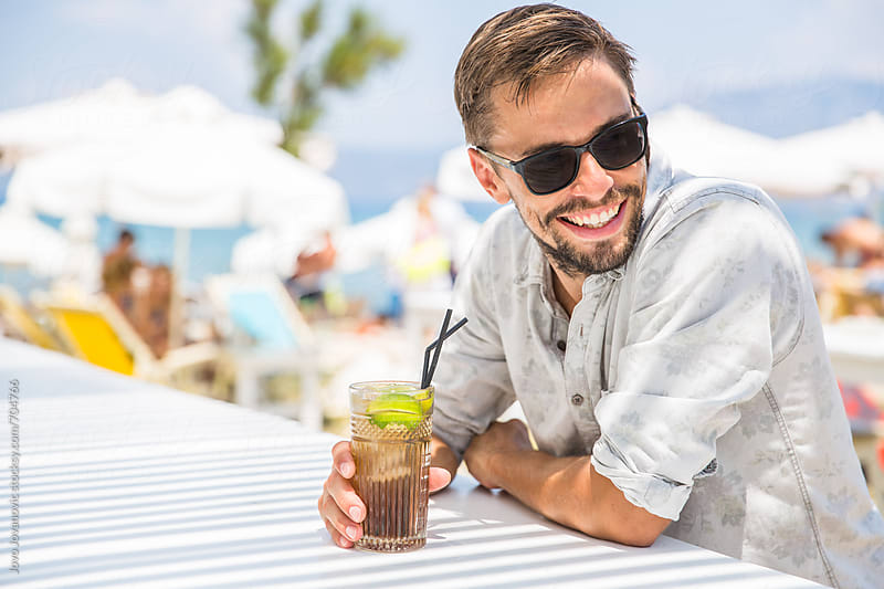 Man drinking cocktail in a tropical bar by Jovo Jovanovic for Stocksy United