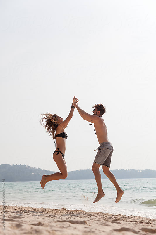 Couple jumping out of joy at the beach by Jovo Jovanovic for Stocksy United