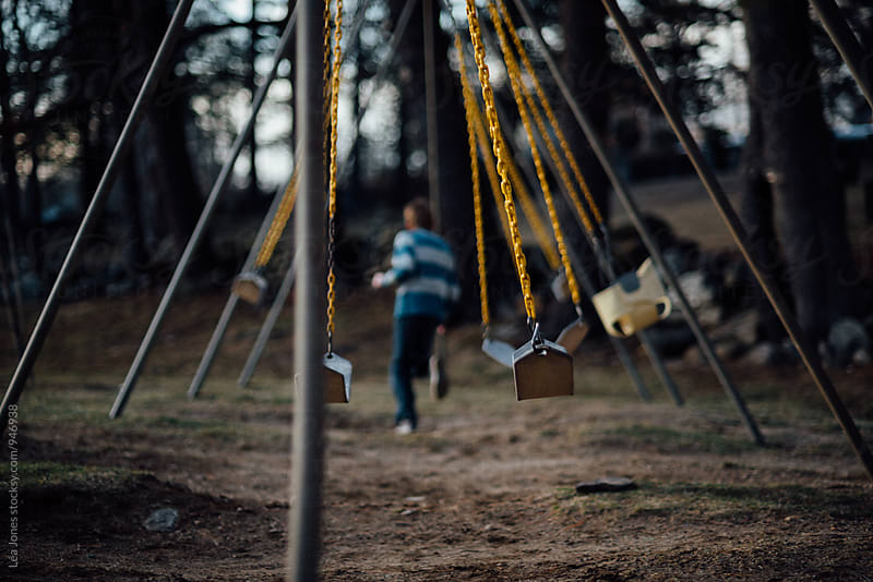 child running through the swings by Léa Jones for Stocksy United