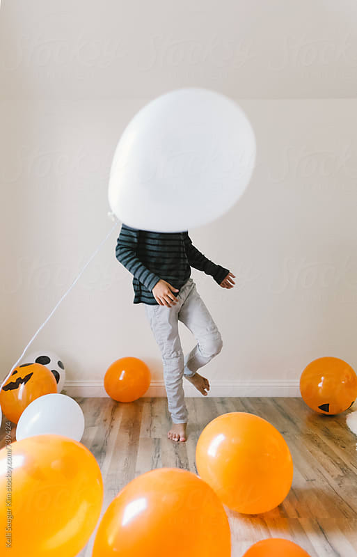 young boy plays with Halloween balloons by kelli kim for Stocksy United