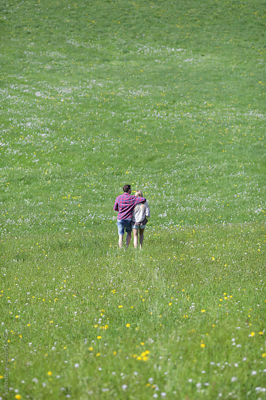 young couple big green meadow hug hugging by rolfo for Stocksy United