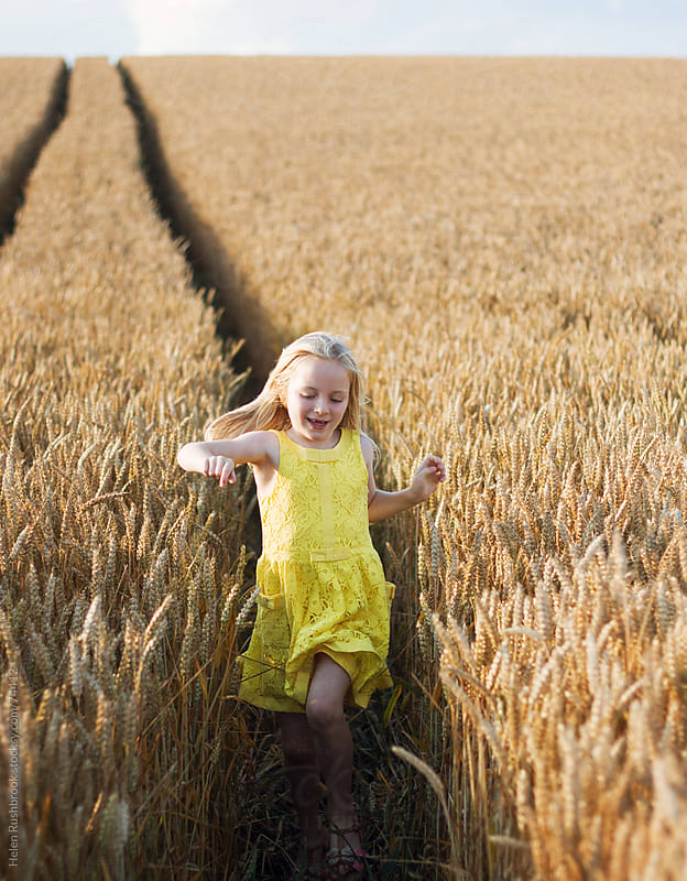 A female child running thought a field of wheat by Helen Rushbrook for Stocksy United