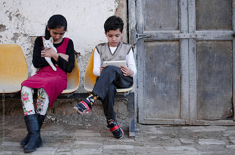 Two children , one holding a white kitten and the other with his tablet ! by Agha Waseem Ahmed for Stocksy United