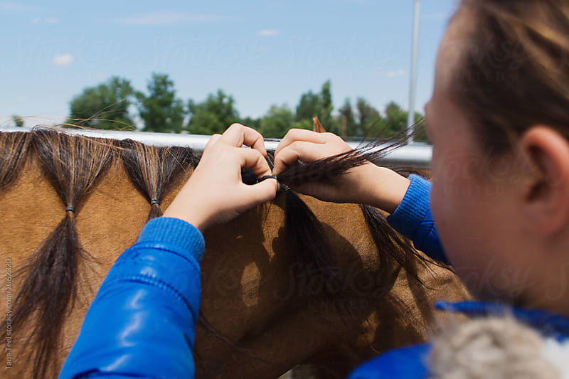girl fixing horse's mane  by Tana Teel for Stocksy United