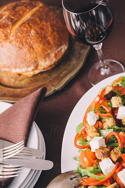 Healthy salad with croutons, glass of red wine and bread by Borislav Zhuykov for Stocksy United