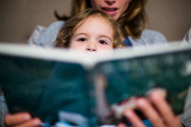 A little girl peeking over a book by Jakob for Stocksy United