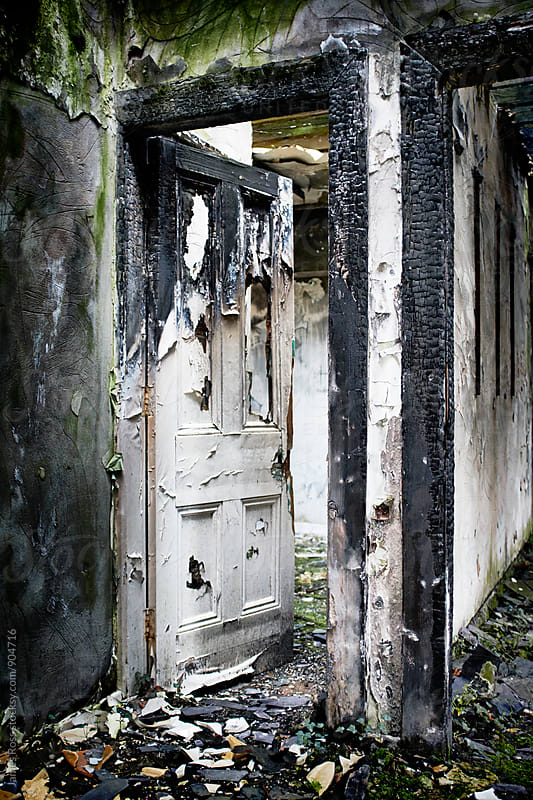 A doorway in a burnt out building by James Ross for Stocksy United