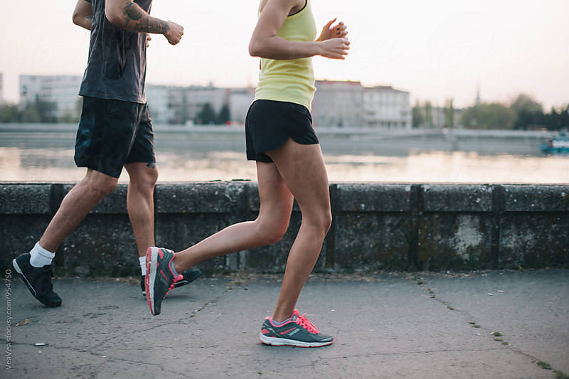 Couple running on a quay by Marija Mandic for Stocksy United
