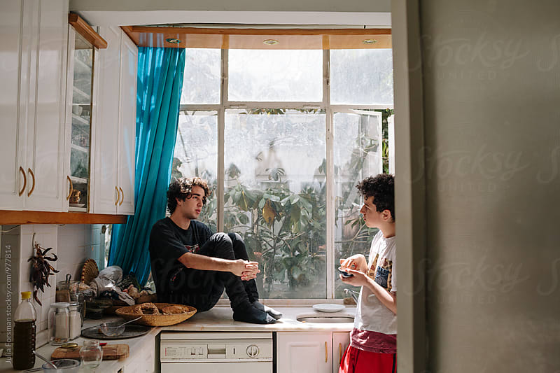 Teenage brothers talk in the kitchen. by Julia Forsman for Stocksy United