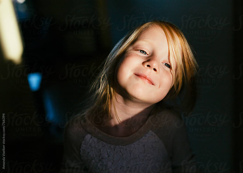 Striking Portrait of  Young Girl in Direct Light and Strong Shadow by Amanda Voelker for Stocksy United