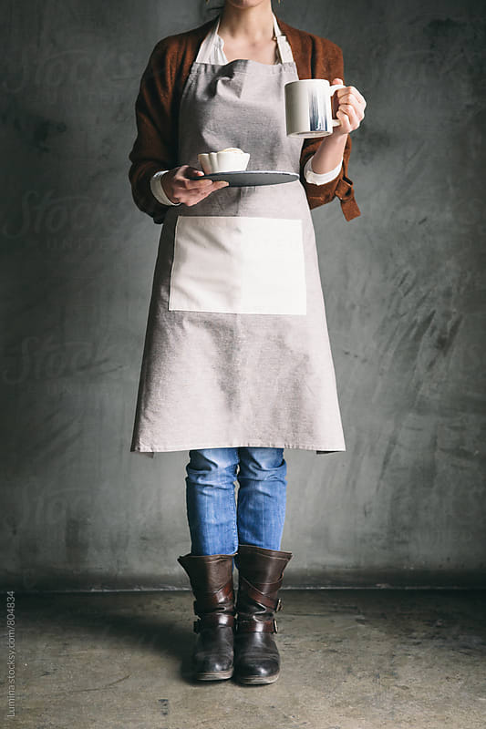 Woman in an Apron Holding Cookies and Coffee by Lumina for Stocksy United