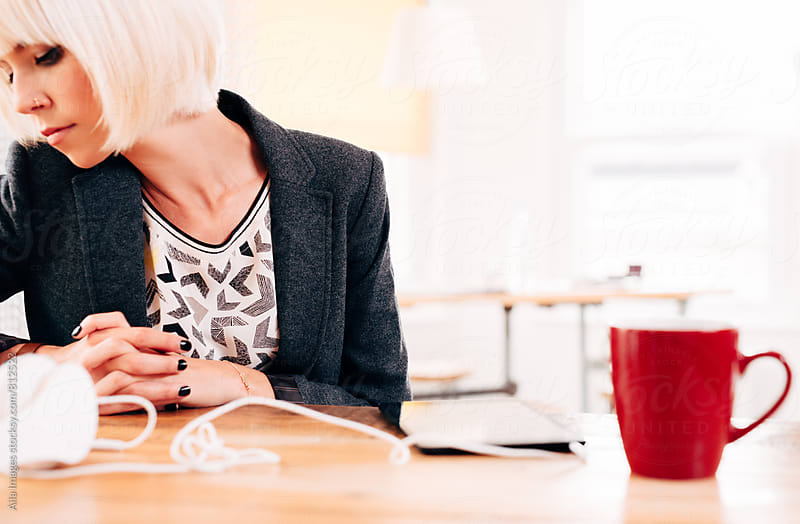 Ambitious Businesswoman working on technology digital tablet device at work startup by Aila Images for Stocksy United