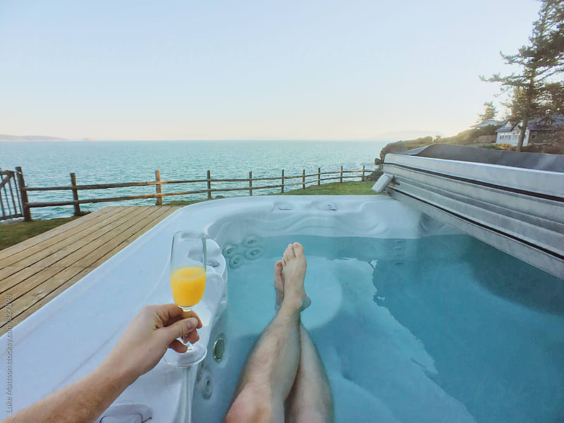 Young Man Holding Mimosa Sitting In Hot Tub With Ocean View by Luke Mattson for Stocksy United