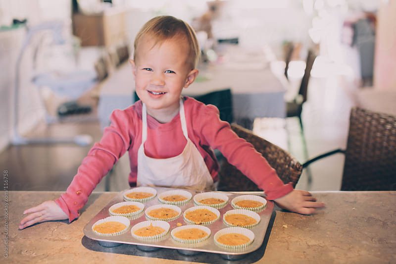Little Girl Making Muffins  by Gabrielle Lutze for Stocksy United