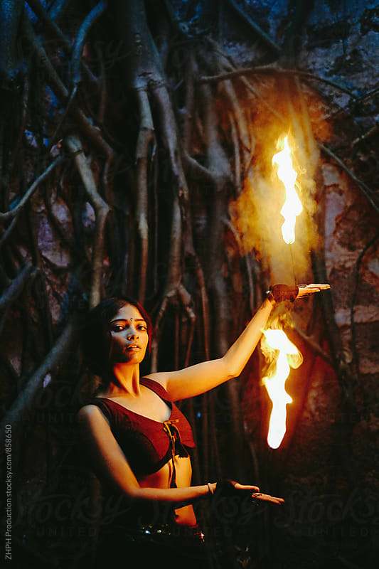 Pretty fire performer with hand flames by Artem Zhushman for Stocksy United
