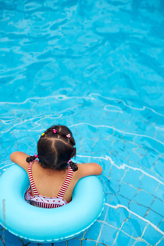 rear view of little asian girl in siting in the ring at the swim by Bo Bo for Stocksy United