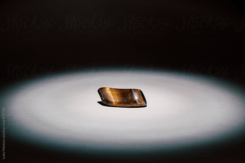 Tiger's Eye Rock Illuminated By Spotlight by Luke Mattson for Stocksy United