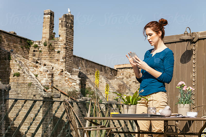 Redhead businesswoman working with digital tablet on a outdoors home office. by BONNINSTUDIO for Stocksy United