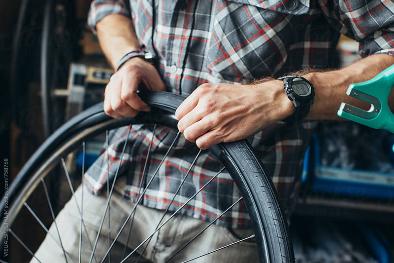 Hands of Young Male Mechanic Assembling Tube and Tire on Bicycle Wheel by Julien L. Balmer for Stocksy United