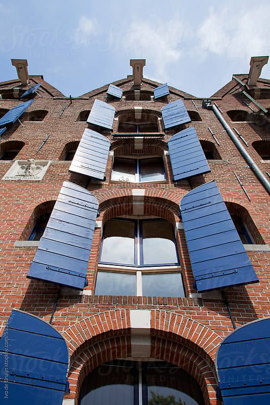 A classic facade of a brick mansion with blue shutters in Amsterdam, photographed from below by Ivo de Bruijn for Stocksy United