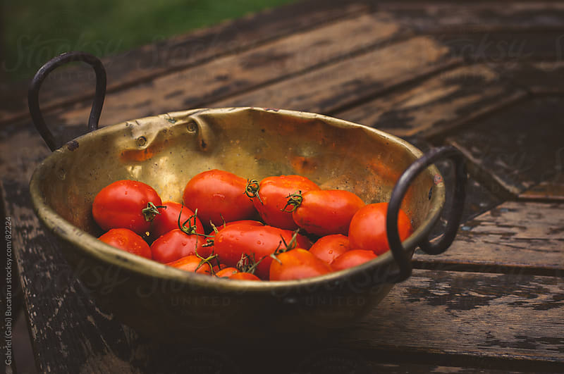 an antique brass bowl with fresh Roma tomatoes by Gabriel (Gabi) Bucataru for Stocksy United