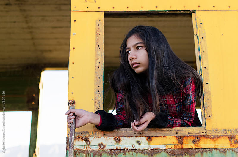 An adolescent girl looking outside a train window ! by Agha Waseem Ahmed for Stocksy United