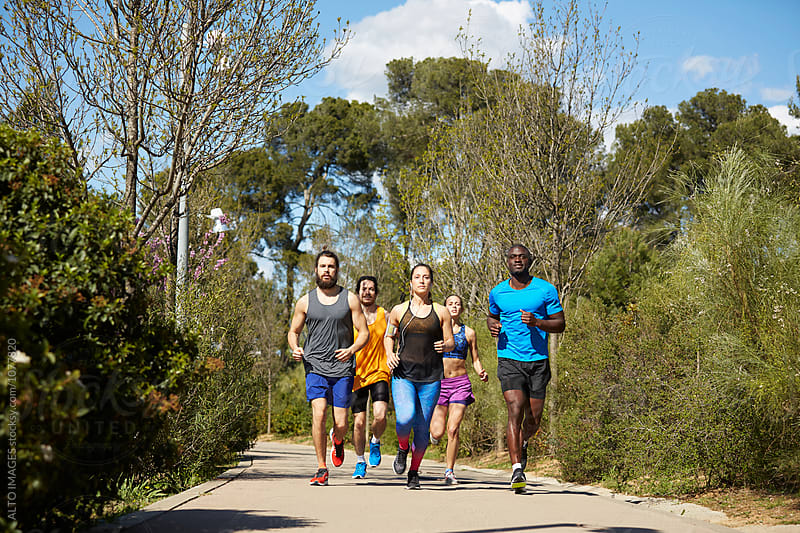 Multiethnic Runners On Street Amidst Trees by ALTO IMAGES for Stocksy United