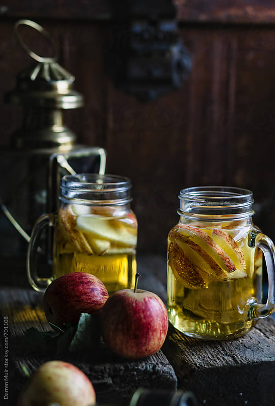 Two jugs of delicious apple cider in a rustic setting. by Darren Muir for Stocksy United
