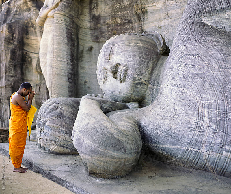 Buddhist monk praying at the Reclining Buddha. Gal Vihara. Polonnaruwa. by Hugh Sitton for Stocksy United