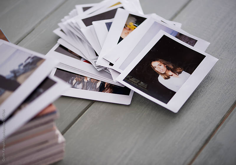bunch of polaroids and magazines on a green wooden table by Guille Faingold for Stocksy United