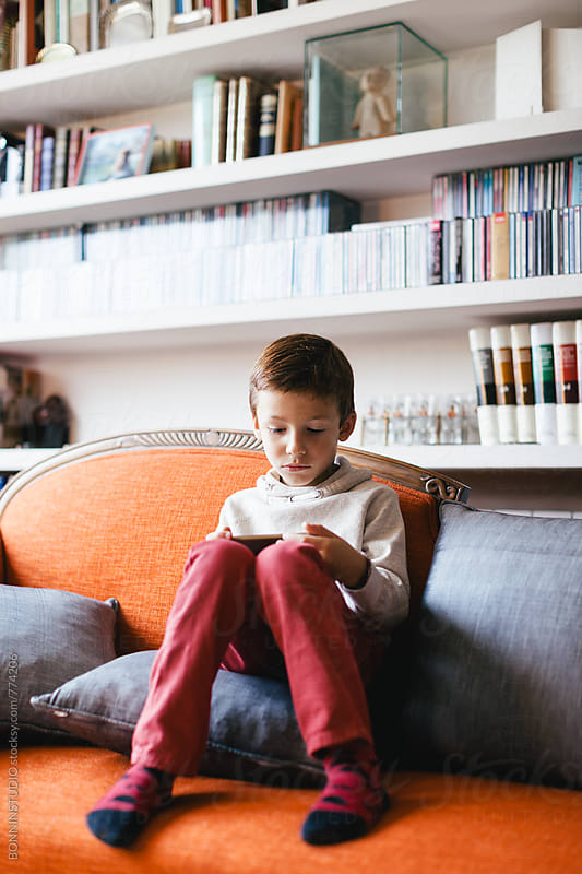 Kid playing with a smartphone sitting on the sofa. by BONNINSTUDIO for Stocksy United