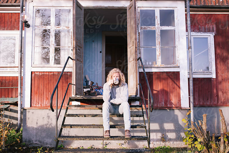 Young man enjoying his coffee outside in the sun. by Koen Meershoek for Stocksy United