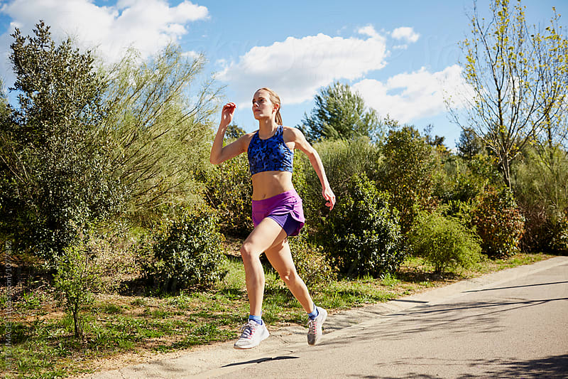 Determined Sporty Woman Jogging On Street by ALTO IMAGES for Stocksy United
