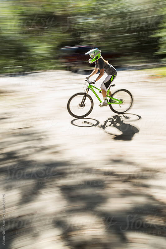 Mountain biker speeding by, motion blur by Adam Nixon for Stocksy United