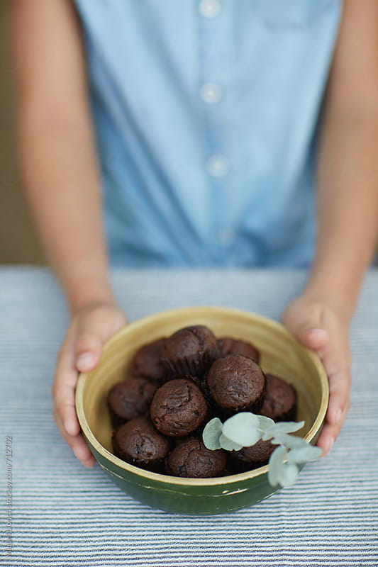 Child holding a bowl with chocolate muffins by Miquel Llonch for Stocksy United