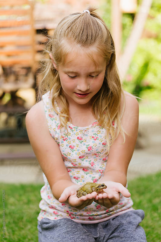 Girl holding frog in garden at home by Kirsty Begg for Stocksy United