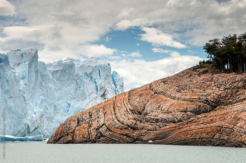 Rocky outcrop scarred by glacial erosion with glacier. by Mike Marlowe for Stocksy United
