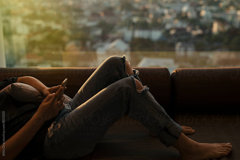 Woman lying on couch texting with city view in the background by Alita Ong for Stocksy United